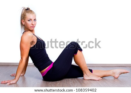young woman making exercises at home on wooden floor - stock photo