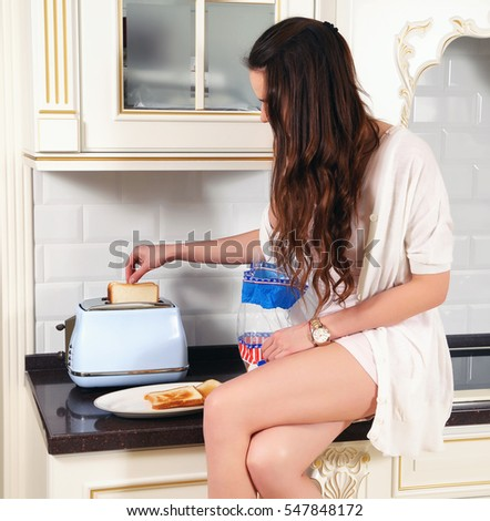 Young woman making  toast bread with toaster at home kitchen