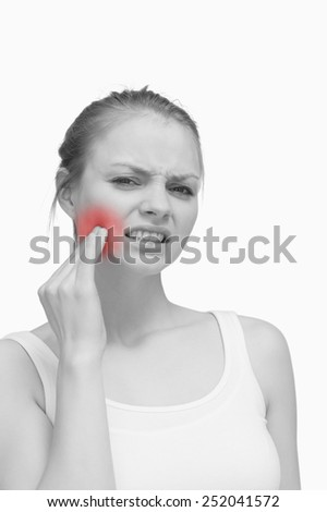 Young woman massaging her jaw against white background - stock photo