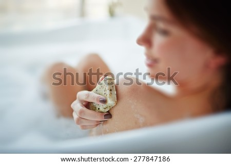 Young woman massaging shoulder skin with exfoliating soap