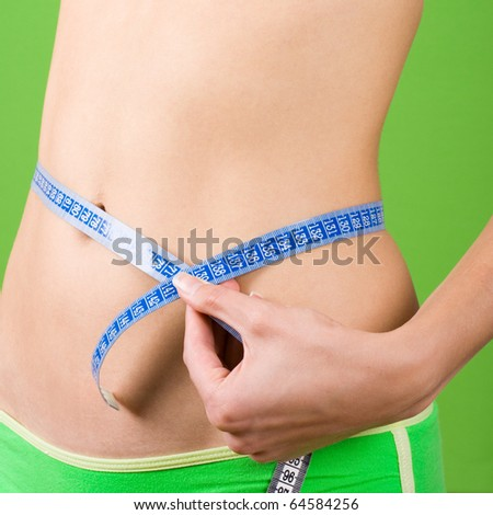 young woman measuring her slim body on green background - stock photo