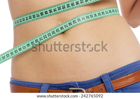 Young woman measuring her waist - stock photo