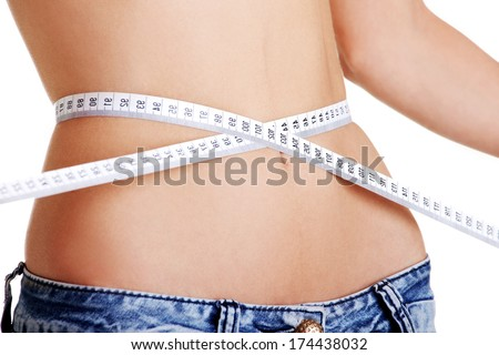 Young woman measuring her waist with tape - stock photo