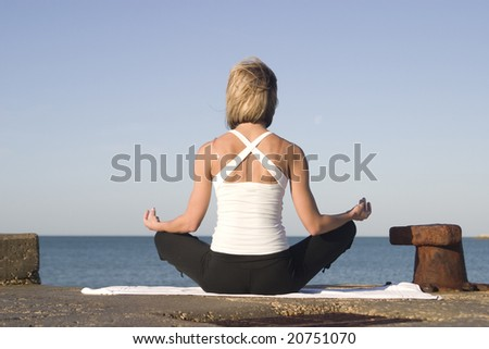 Young woman meditates in lotos position next to the sea - stock photo