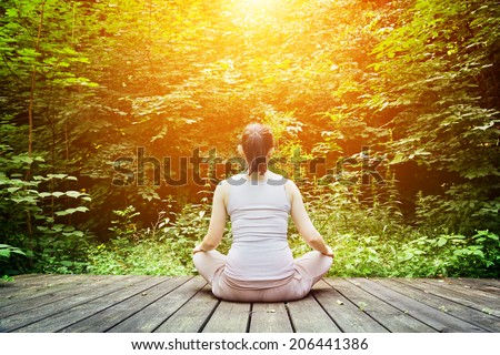 Young woman meditating in a forest sitting on a wooden floor. Zen, meditation, relax, spiritual health, healthy breathing - stock photo