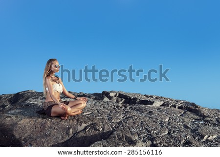 Young woman meditating in lotus position sitting on beach rock - stock photo