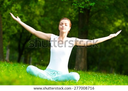 Young woman meditating in park.  - stock photo