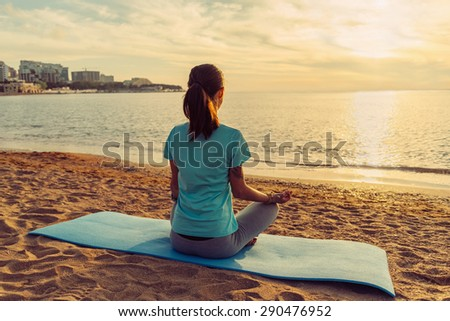 Young woman meditating in pose of lotus on sand beach near the sea at sunset in summer - stock photo