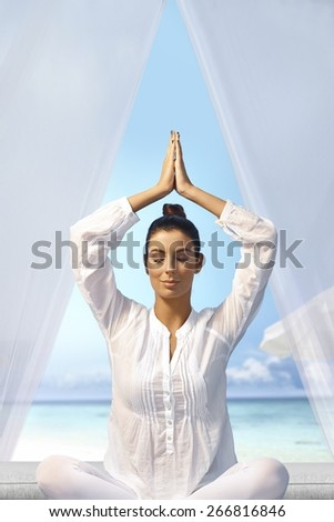 Young woman meditating in prayer position eyes closed on the beach. - stock photo