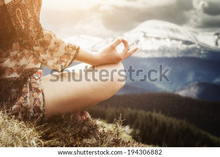 Young woman meditating in the mountains - stock photo