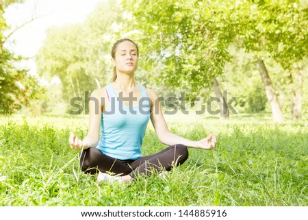 Young woman meditating in the park. - stock photo