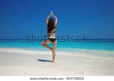 Young Woman meditating in tree yoga position on the exotic beach. Zen, meditation, peace. Balance. Bliss freedom concept.  - stock photo