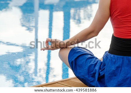 Young woman meditating on a wooden deck - stock photo