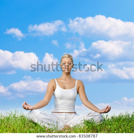 Young woman meditating on green grass with copyspace. - stock photo