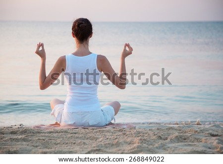 Young woman meditating on the sea coast at dawn - stock photo