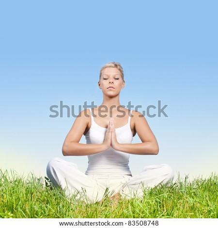 Young woman meditating outdoors with copyspace.