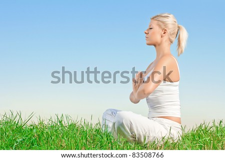 Young woman meditating outdoors with copyspace. - stock photo
