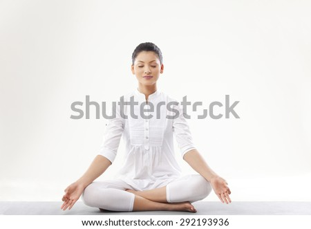 Young woman meditating over white background - stock photo