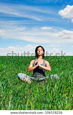 young woman meditation on green meadow - stock photo