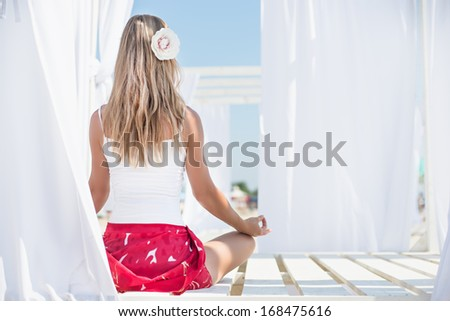 Young woman meditation on the beach - stock photo