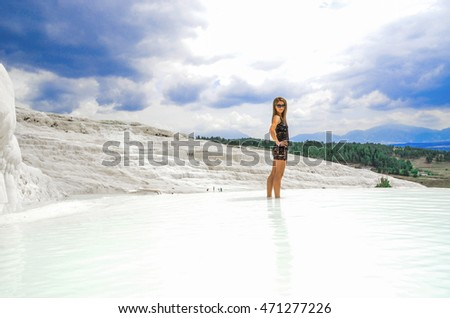 Young woman model in front of travertine at Pamukkale, Turkey