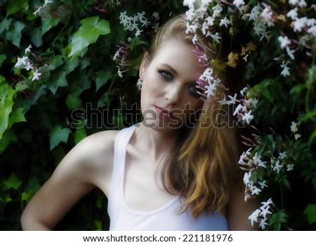 Young woman model standing among flowers - stock photo
