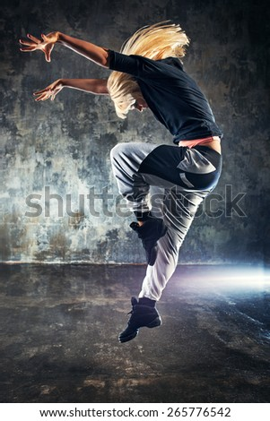 Young woman modern dancer jumping. On dark stone wall background. - stock photo