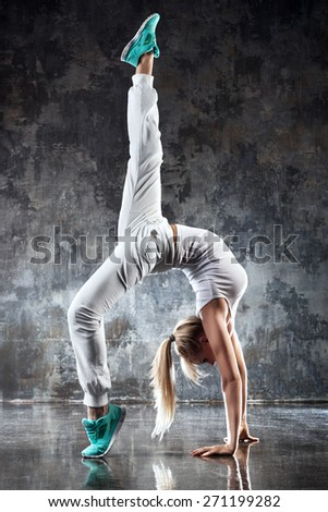 Young woman modern dancer. On stone wall background. - stock photo
