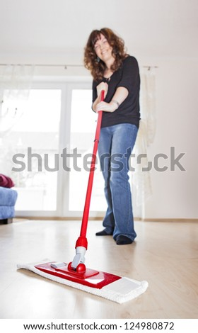 Young woman mopping the floor