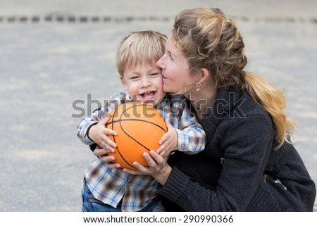 Young woman - mother, kissing and hugging her little son, holding a basket ball. - stock photo