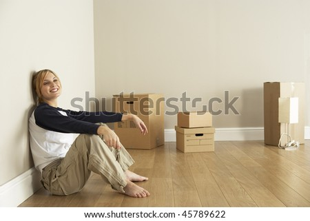 Young Woman Moving Into New Home - stock photo