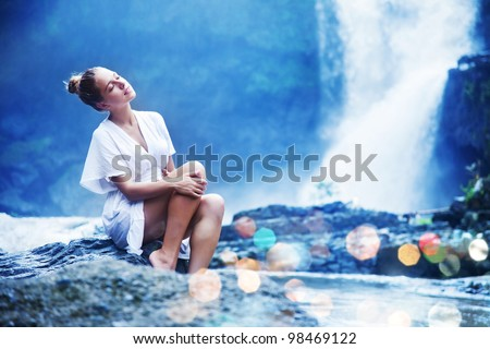 Young woman near waterfall, bali, indonesia - stock photo