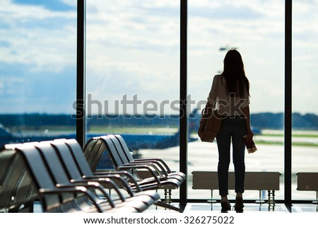 Young woman near window in an airport lounge waiting for flight aircraft - stock photo