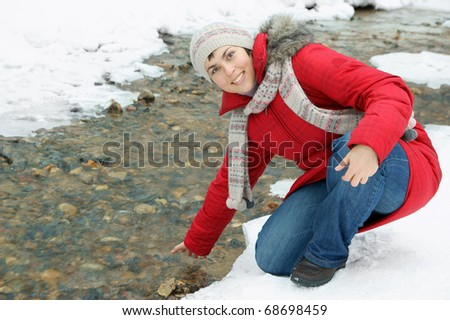 Young woman near winter river - stock photo
