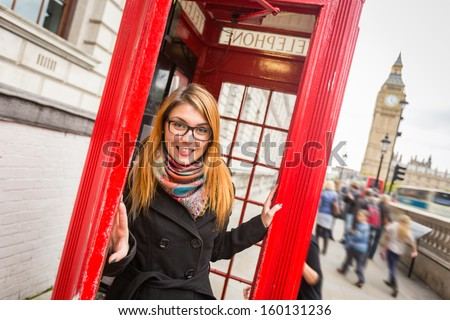 Young Woman next to London Traditional Telephone Booth - stock photo