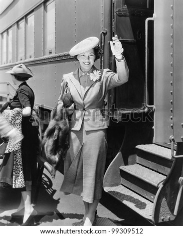 Young woman next to train waving