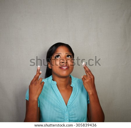 Young woman of afro-american ethnicity praying while crossing her fingers - copy space - stock photo