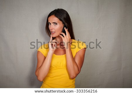 Young woman of caucasian ethnicity planning while speaking on cell phone - stock photo