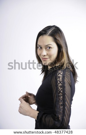 Young woman of filipino ethnicity is standing sideways and looking at camera. - stock photo
