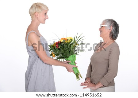 Young woman offering a bouquet of flowers to her grandmother - stock photo