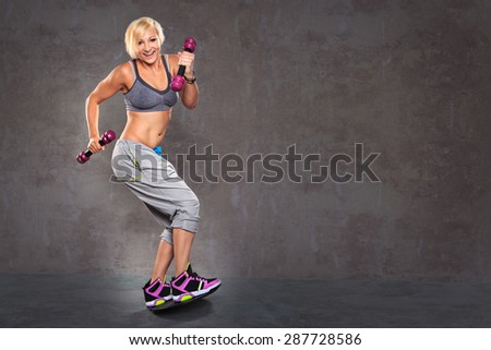 young woman on a balance board with barbells - stock photo