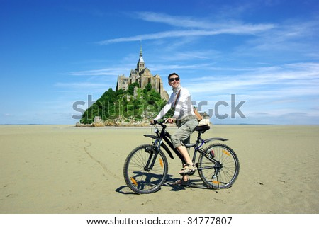 Young woman on a bicycle on a background of the Mont Saint Michel - stock photo