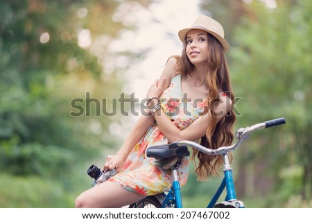 Young woman on a bicycle using a camera to take photo at the park