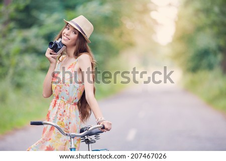 Young woman on a bicycle using a camera to take photo at the park - stock photo