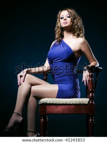 Young woman on a chair. On dark background.