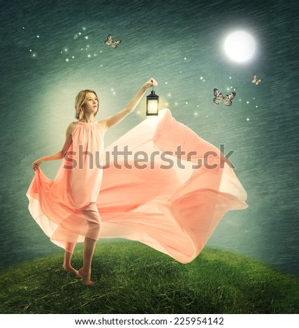 Young woman on a fantasy grassy hilltop with antique lamp - stock photo