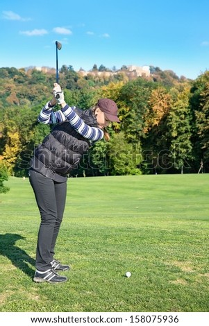 Young woman on a golf course on a sunny autumn day in the background of the old castle - stock photo