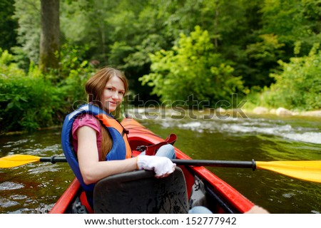 Young woman on a kayak at summer - stock photo