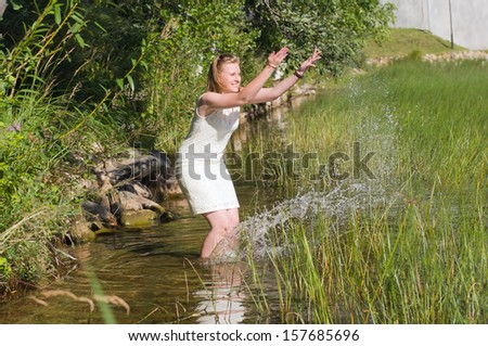 Young woman on a lake bank playing with water.