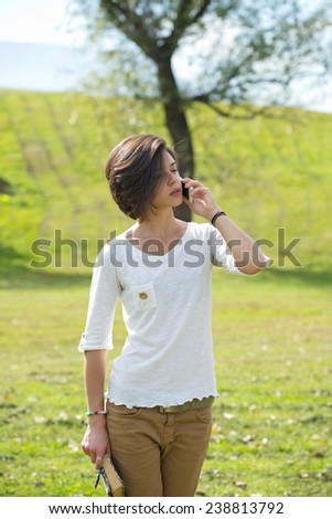 Young woman on a mobile phone walking in a park. - stock photo